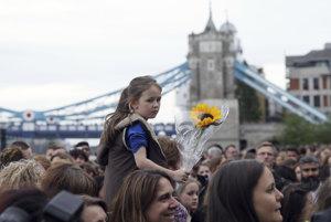 Ľudia zhromaždení na nábreží Temže neďaleko Toweru v parku Potters Filed kladú kvety po vigílii za obete sobotňajšieho útoku v Londýne.