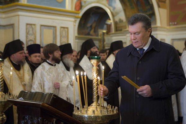 Ukrajinský prezident Viktor Janukovyč zapaľuje sviečky počas omše pri príležitosti osláv Dňa jednoty a slobody v katedrále Nanebovzatia Panny Márie v Kyjev.