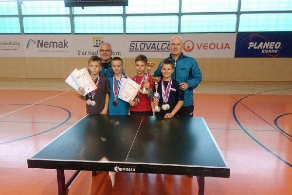 Stolní tenisti Topoľčian s trofejami z M-SR najmladšieho žiactva. V popredí zľava: Samuel Arpáš, Martina Igazová, Alexander Katona a Krisitán Uherík. Za nimi tréneri Jozef Kudrec (vľavo) a Anton Kutiš.