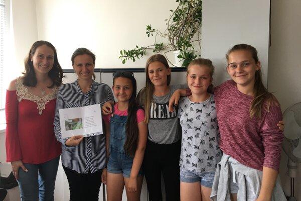 Triedna učiteľka a žiačky zo 6.B si prevzali symbolickú poukážku z rúk Barbory Rumpli zo Slovenských elektrární.