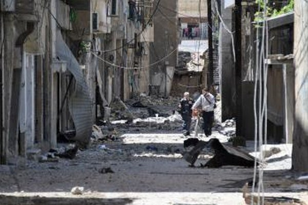 Sýrčania kráčajú okolo zničených budov po ostreľovaní sýrskymi vládnymi silami na ulici v sýrskom meste Homs.