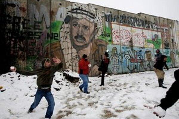 Palestínčania sa guľujú pred bezpečnostnou bariérou pri Jeruzaleme.