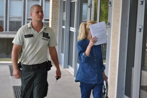 Eskorta s obvinenou. Privádzajú ju na súd.
