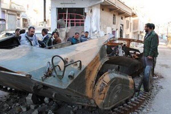 Povstalci pri zničenom obrnenom vozidle sýrskej armády.