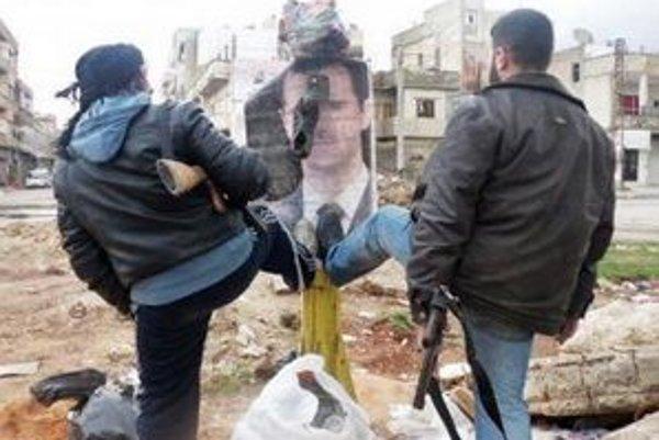 Sýrski povstalci kopú do portrétu sýrskeho prezidenta Bašára Asada v provincii Idlib.