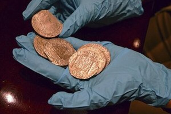 Člen technického tímu španielskeho ministerstva ukazuje zopár mincí z celkovej zbierky 594.000 vzácnych strieborných mincí.