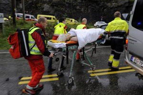 Záchranári pomáhajú zranenej tínedžerke na ostrove Utöya.