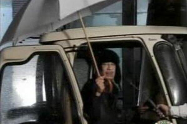 Líbyjský diktátor sa v pondelok v noci nachvíľu ukázal v bizarnom vystúpení pod dáždnikom pred svojím domom.