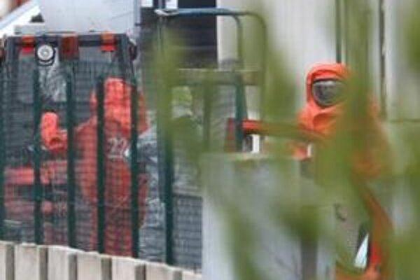 Záchranári v protichemických oblekoch.