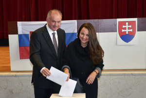 Andrej Kiska vhadzuje lístok do urny spolu so svojou manželkou.
