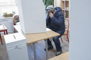 Volič telefonuje v priestore určenom na úpravu hlasovacích lístkov počas volieb do orgánov samosprávnych krajov.