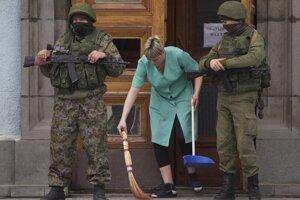 Žena zametá pred budovou miestnej vlády na Kryme.