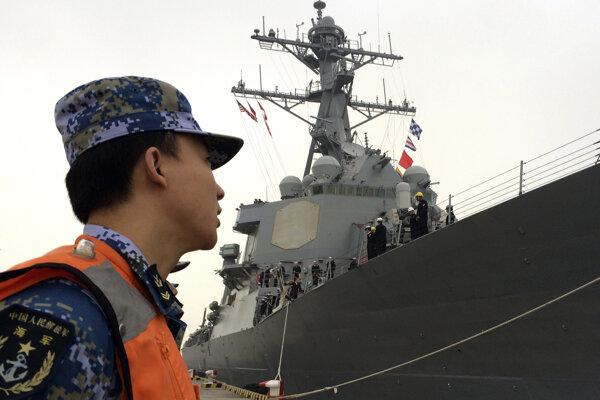 Čínsky vojak sleduje americkú loď USS Stethem.