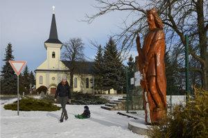 Na snímke časť Kráľovskej aleje sôch v obci Čečejovce, v okrese Košice-okolie. Vpravo stojí drevená socha kráľa Ladislava I. Svätého, vľavo je rímskokatolícky kostol.