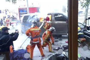 Zásah hasičov pri horiacom aute, ktoré zranilo chodcov v Šanghaji.