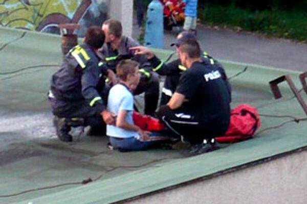 Hasiči a policajti museli chlapca zniesť zo strechy obchodu.