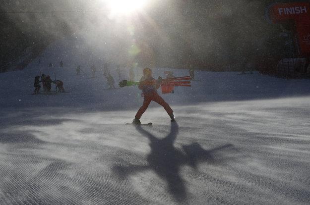 Traťový pracovník odnáša bránky zo svahu obrovského slalomu žien, ktorý z dôvodu silného vetra preložili.