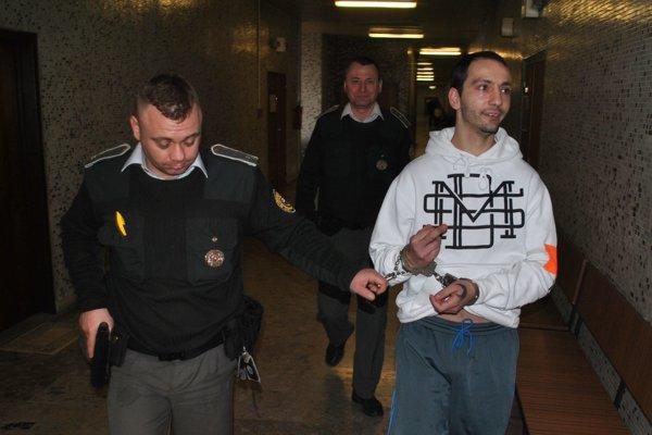 Marek s eskortou. Odvádza ho späť do väzby.