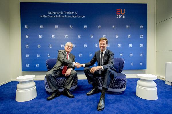 Holandský premiér Mark Rutte (vpravo) si podáva ruku s predsedom Európskej komisie Jeanom-Claudeom Junckerom.