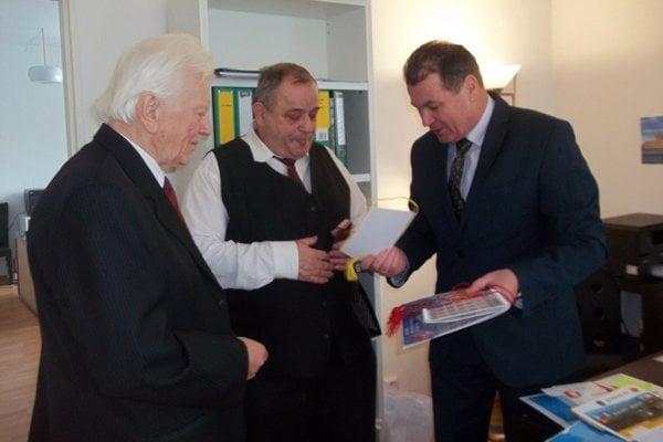 Jozef Křivánek (v strede) aMilan Paršo (vľavo) preberajú ocenenie zrúk Nikolaja Ryžova.