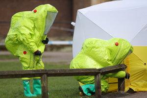 Pracovníci v špeciálnych oblekoch pri použití jedovatej látky.