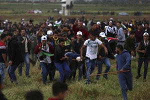Palestínčania odnášajú jedného z protestujúcich, ktorého postrelili izraelskí vojaci.