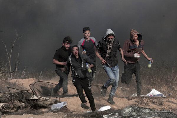Protestujúci Palestínčania unikajú pred zásahom izraelských ozbrojených zložiek.