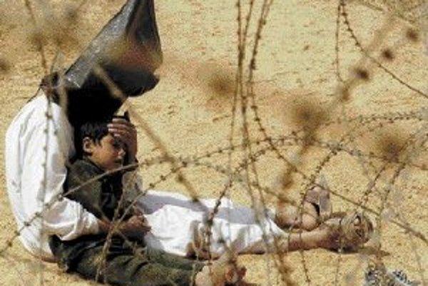 Fotografia francúzskeho fotografa Jeana-Marca Boujua získala roku 2004 hlavnú cenu v súťaži World Press Photo. Na snímke zadržaný Iračan s vrecom na hlave upokojuje syna v tábore vojnových zajatcov v Nadžafe.