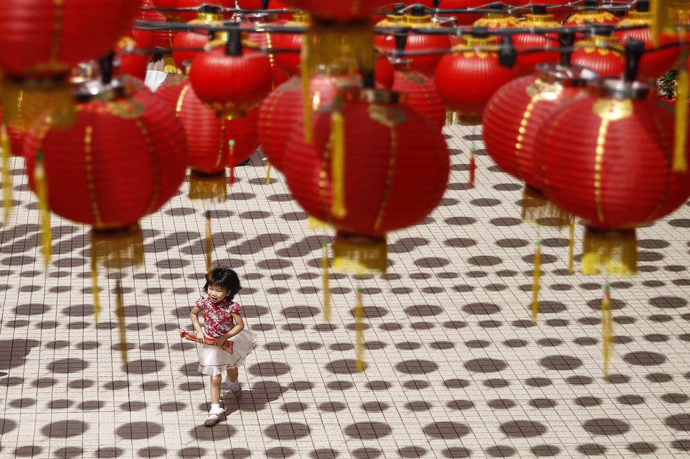 Malé dievčatko sa hrá pod tradičnými čínskymi lampiónmi v Kuala Lumpur.