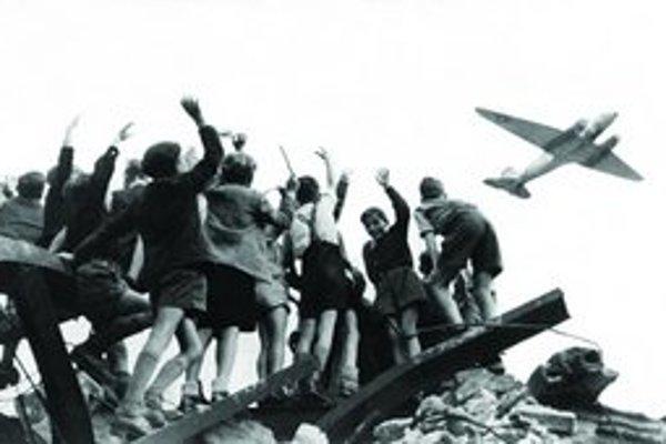 Deti chytajú sladkosti na letisku Tempelhof. Fotografia Henryho Riesa sa stala symbolom leteckého mosta.