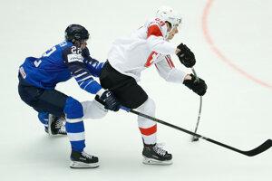 Fín Janne Pesonen (vľvo) v súboji o puk so Švajčiarom Timom Meierom.