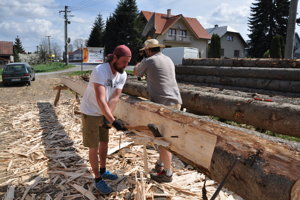 Tesanie trámov na novú drevenicu.