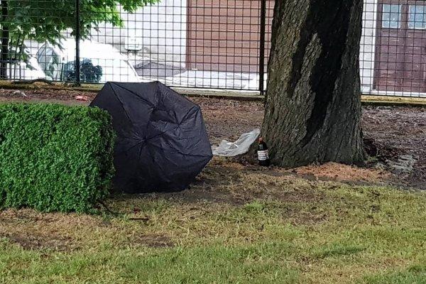 Muž stál pod stromom aj s dáždnikom.