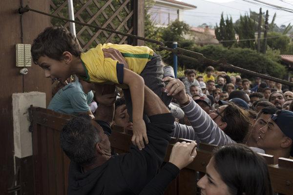 Mldý  brazílsky fanúšik sa tlačí cez bariéru na tréning reprezentantov.