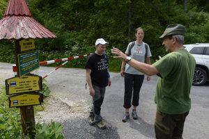 Vedúci Ochranného obvodu Tatranská Javorina Štátnych lesov TANAP-u Ján Slivinský upozorňuje poľských turistov v Javorovej doline na uzáveru chodníkov a konzultuje s nimi možné turistické trasy.