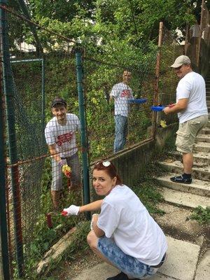 Dobrovoľníci v Nitre s úsmevom  a nasadením života zamaľujú aj diery v plote. Maľuje sa v ZŠ sv. Marka, Nitra.