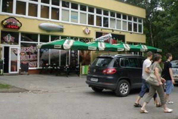 Autá na chodníku prekážajú chodcom pred herňou na Vlčincoch.