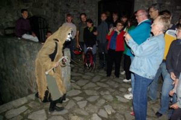 Smrtka a turisti počas nočnej prehliadky hradu.