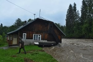 Rozvodnený potok Javorinka berie so sebou starší dom v Podspádoch vo Vysokých Tatrách.