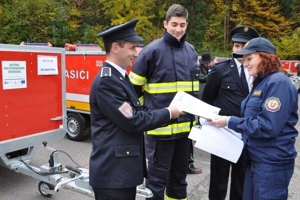 Dušan Buš, veliteľ DHZ v Hladovke, preberá dokumenty od vozíka.