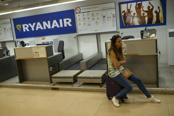 Žena sedí na kufri pri odbavovacom priestore leteckej spoločnosti Ryanair na medzinárodnom letisku Adolfo Suarez-Barajas v Madride.