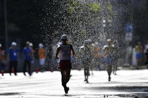 Pretekári kráčajú na trati cez vodnú sprchu počas pretekov v chôdzi mužov na 50 km.