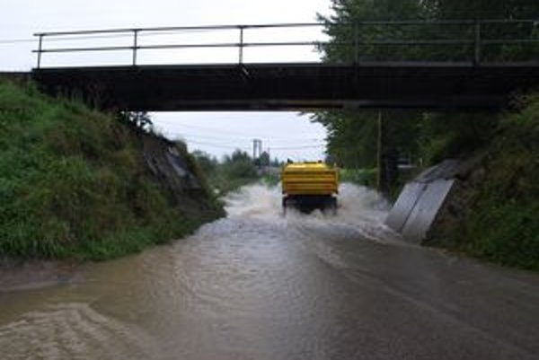 Potok nápor vody znova nevydržal. Tečie po ceste.