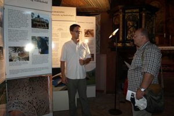 Krátko po nainštalovaní výstavy prišli do dreveného kostolíka prví návštevníci. Výklad k nej im podal László Juhász (vľavo).