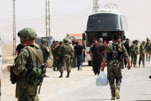 Na snímke ruskí vojaci a sýrske vládne sily sú pred autobusmi počas odchodu islamistických povstalcov z mesta Dumajr 19. apríla 2018.