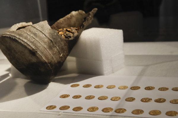 Rozbitá nádoba a prvých 27 mincí, ktoré archeológovia oddelili.