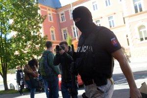 Člen špeciálnej jednotky (vpravo) počas výsluchu štvorice obvinených na Špecializovanom trestnom súde v Banskej Bystrici.