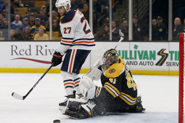 Brankár Bostonu Bruins Jaroslav Halák a jeho zákrok proti Milanovi Lucicovi z Edmontonu Oilers.