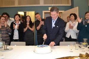 Miloš Meričko krája tortu pre víťaza.