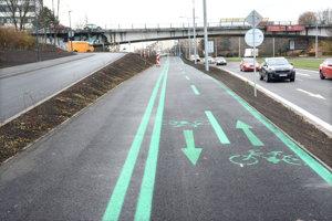 Cyklisti volajú po zábradlí medzi cyklochodníkom a cestou, ktoré by ich chránilo.
